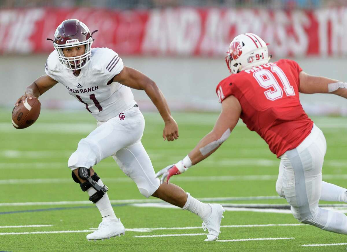 Cam Harper (11) of the Cinco Ranch Cougars scrambles away from Michael Matus (91) of the Katy Tigers in the first half of a high school football game on Friday, September 22, 2017 at Legacy Stadium in Katy Texas.