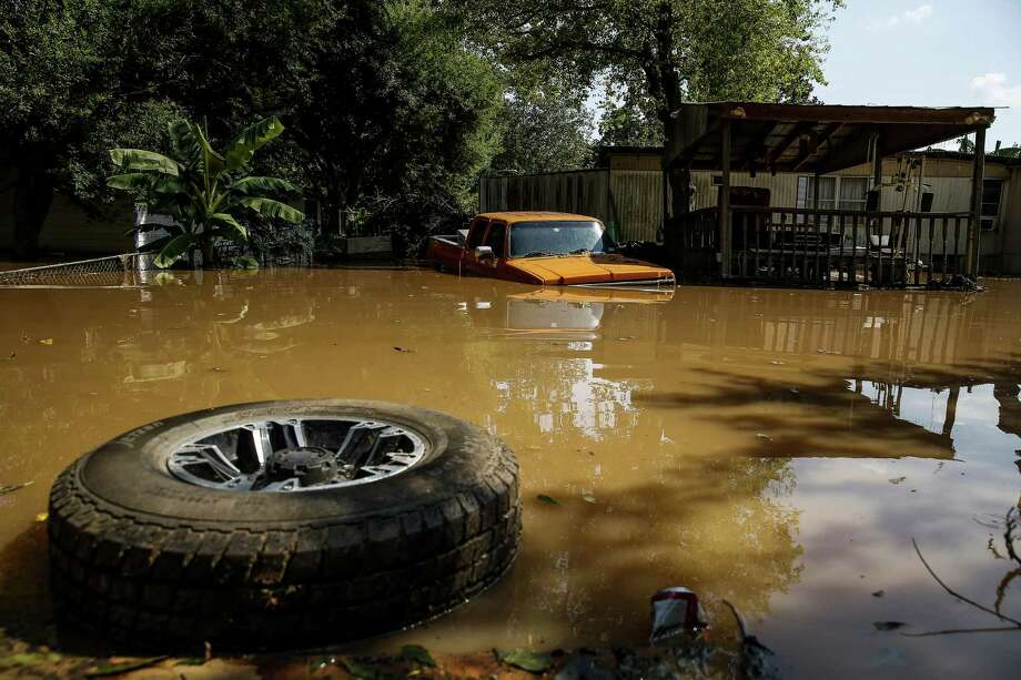 A tire floats next to a truck flooded by the Brazos River after Tropical Storm Harvey Sept. 1 in Richmond. The organic status of this year's rice crops in Texas was at risk due to the mass aerial spraying to control mosquitoes hatching eggs in all the standing post-Harvey flood waters in Southeast Texas. Photo: Michael Ciaglo /Houston Chronicle / Michael Ciaglo