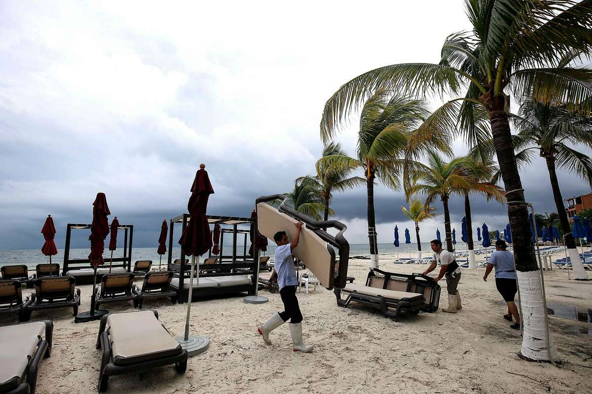 Hotel staffers collect beach loungers and sunshades before the arrival of tropical storm Nate, in Cancun, Quintana Roo state, Mexico on October 6, 2017. Tropical Storm Nate gained strength Friday as it headed toward popular Mexican beach resorts and ultimately the US Gulf coast after dumping heavy rains in Central America that left at least 22 people dead. / AFP PHOTO / ELIZABETH RUIZELIZABETH RUIZ/AFP/Getty Images