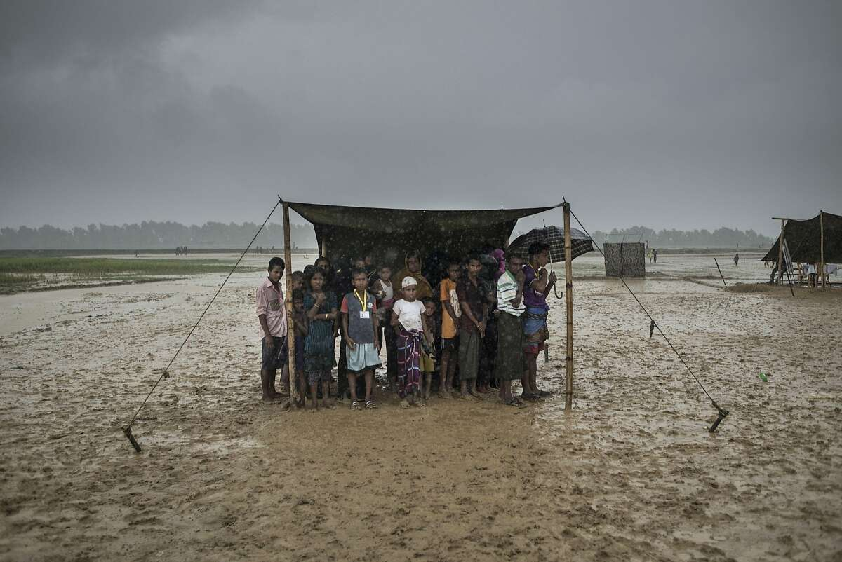 Rohingya Muslim refugees take shelter from the rain during a food distribution at Nayapara refugee camp in Bangladesh's Ukhia district on October 6, 2017. Bangladesh on October 5 announced it would build one of the world's biggest refugee camps to house all the 800,000-plus Rohingya Muslims who have sought asylum from violence in Myanmar. The arrival of more than half a million Rohingya Muslims from Buddhist-dominated Myanmar since August 25 has put an immense strain on camps in Bangladesh where there are growing fears of a disease epidemic. / AFP PHOTO / FRED DUFOURFRED DUFOUR/AFP/Getty Images