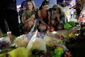 People pause at a memorial set up for victims of a mass shooting in Las Vegas, Nev., on Tuesday, Oct. 3, 2017. A gunman opened fire on an outdoor music concert on Sunday. It was the deadliest mass shooting in modern U.S. history, with dozens of people killed and hundreds injured, some by gunfire, some during the chaotic escape. (AP Photo/John Locher) ORG XMIT: NVSM135