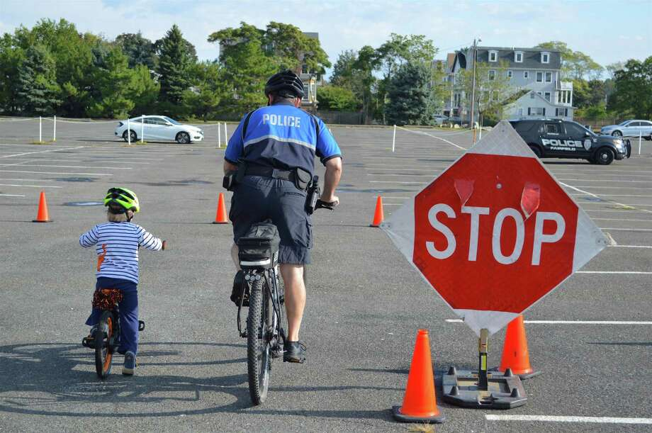 Officer Dan Gulino of New Canaan shows Sam Oleksiw, 5, of Fairfield, how bicyclists should stop at stop signs at the Youth Bicycle Safety Rodeo at Jennings Beach, Saturday, Sept. 30, 2017, in Fairfield, Conn. Photo: Jarret Liotta / For Hearst Connecticut Media / Fairfield Citizen News Freelance