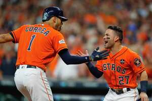 Houston Astros shortstop Carlos Correa (1) and second baseman Jose Altuve (27) celebrate Correa's two-run home run that drove in Altuve during the first inning of Game 1 of the ALDS at Minute Maid Park on Friday, Oct. 6, 2017, in Houston.