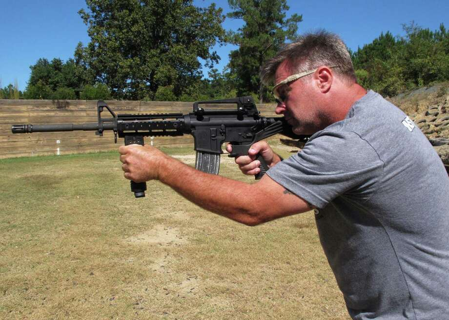 """Shooting instructor Frankie McRae aims a rifle fitted with a """"bump stock"""" in Bunnlevel, N.C., on Wednesday. This is the kind of stock Las Vegas shooter Stephen Paddock used to simulate automatic fire. What can we expect Congress and the president to do about this? Nothing. Americans' only recourse is to change the balance of power in Washington. Photo: Allen G. Breed /Associated Press / Copyright 2017 The Associated Press. All rights reserved."""