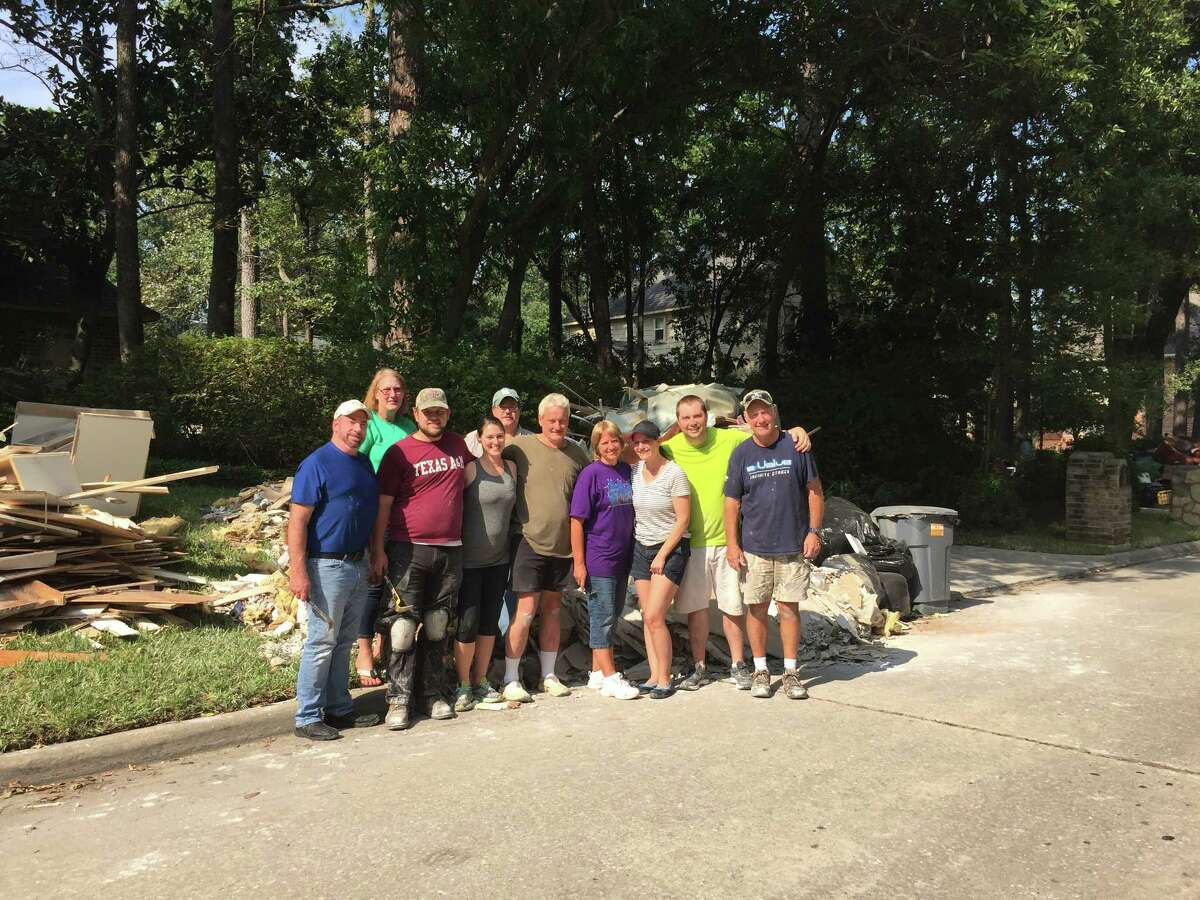 Volunteers stand outside Bradford T. Laney's house in Kingwood after helping with demolition and clean up efforts after Laney's home flooded.