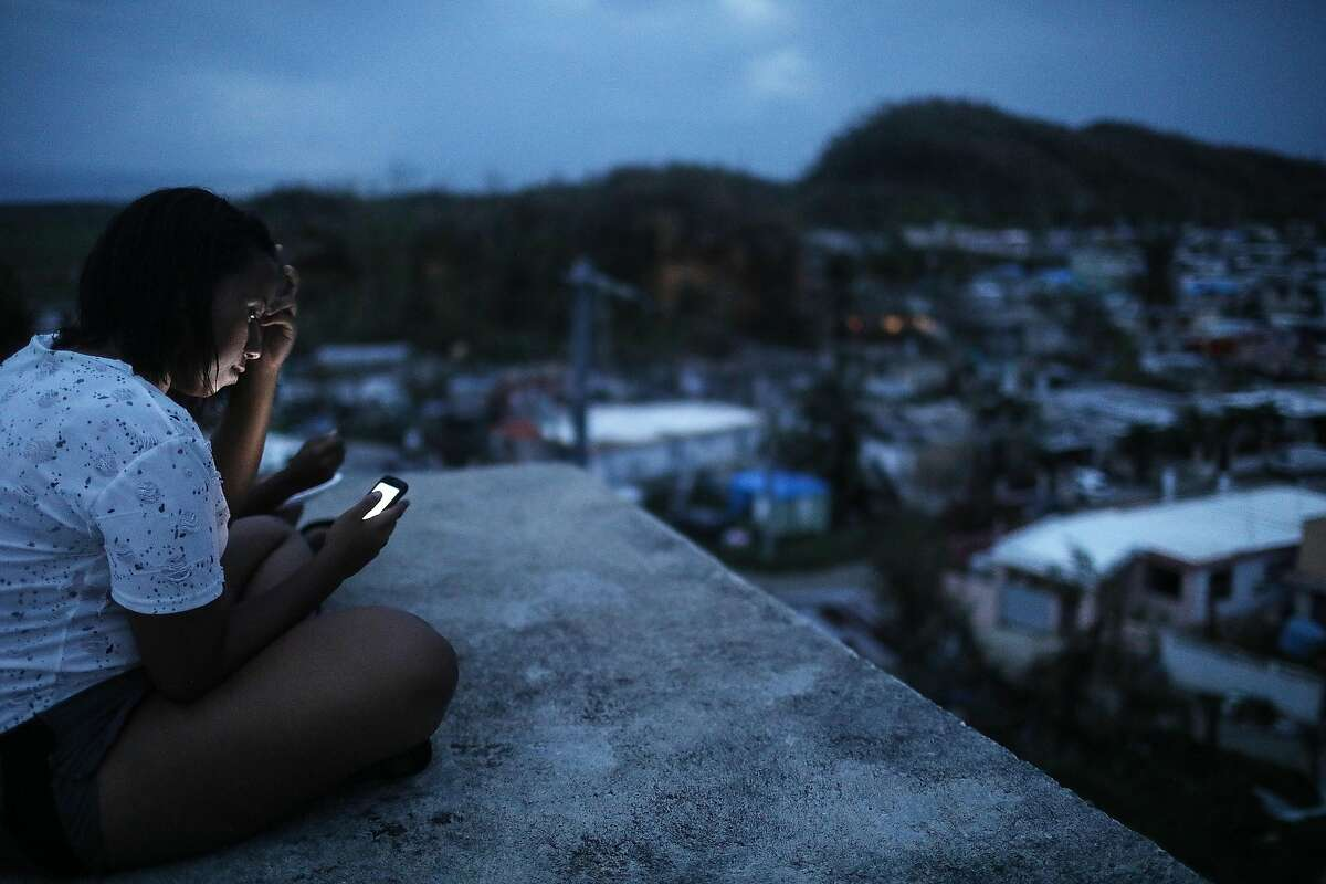 SAN ISIDRO, PUERTO RICO - OCTOBER 05: A resident checks her cell phone on her rooftop at dusk about two weeks after Hurricane Maria swept through the island on October 5, 2017 in San Isidro, Puerto Rico. Residents in her section of the town remain without grid power or running water although a few have been able to acquire generators for power. Puerto Rico experienced widespread damage including most of the electrical, gas and water grid as well as agriculture after Hurricane Maria, a category 4 hurricane, swept through. (Photo by Mario Tama/Getty Images)