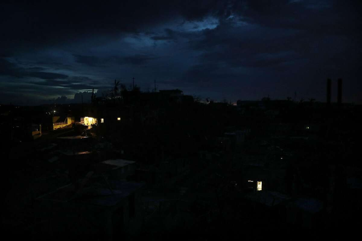 SAN ISIDRO, PUERTO RICO - OCTOBER 05: A house (Upper Left) is lit by a generator in a neighborhood without grid power or running water about two weeks after Hurricane Maria swept through the island on October 5, 2017 in San Isidro, Puerto Rico. A few residents have acquired generators for electricity in the area but most homes remain dark. Puerto Rico experienced widespread damage including most of the electrical, gas and water grid as well as agriculture after Hurricane Maria, a category 4 hurricane, swept through. (Photo by Mario Tama/Getty Images)