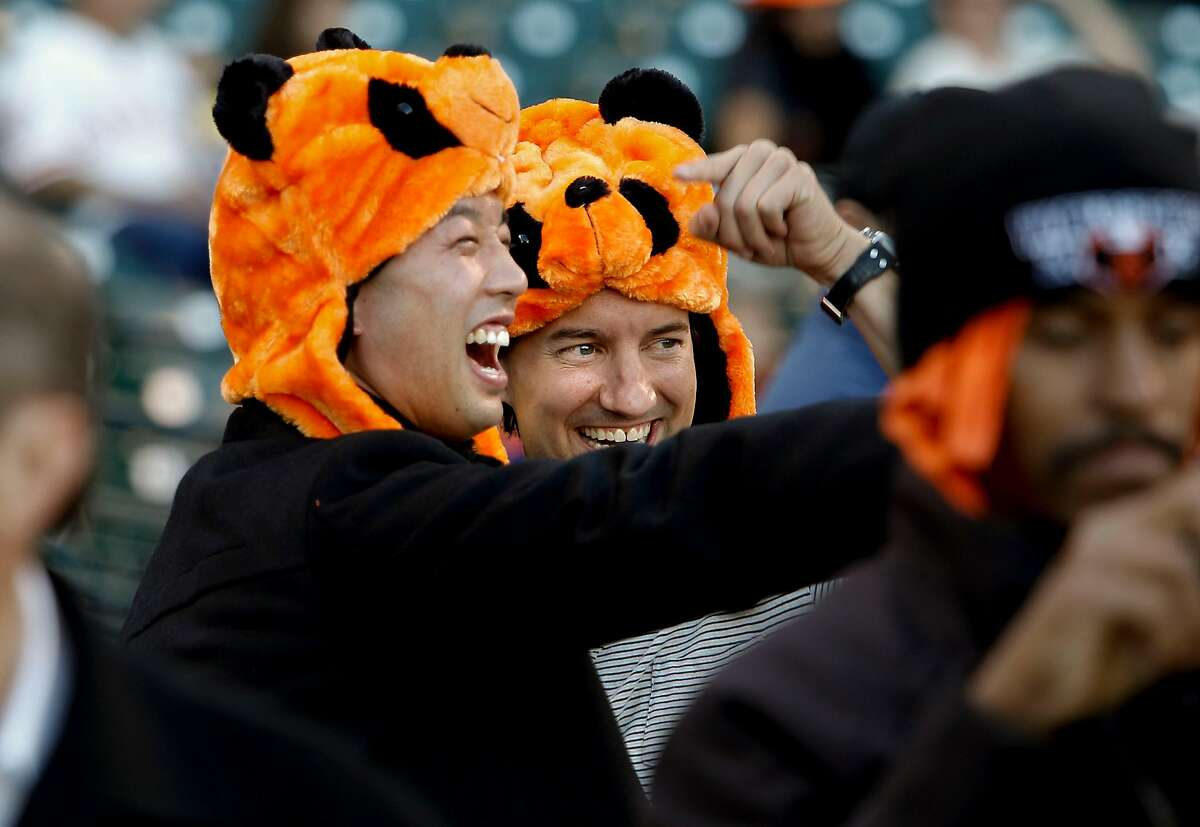 Howard Wang and Will Kozicki, of Los Angeles, share a laguh while wearing their orange Panda hats, as the San Francisco Giants prepares to take on the Detroit Tigers in game two of the World Series, on Wednesday Oct. 24, 2012 at AT&T Park, in San Francisco, Calif.