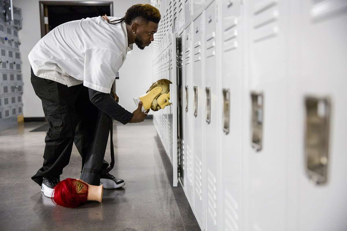 Jamahl Mackey stores the mannequin heads in his locker at the Federico Beauty Institute on Thursday, Sept. 28, 2017, in Sacramento, Calif.
