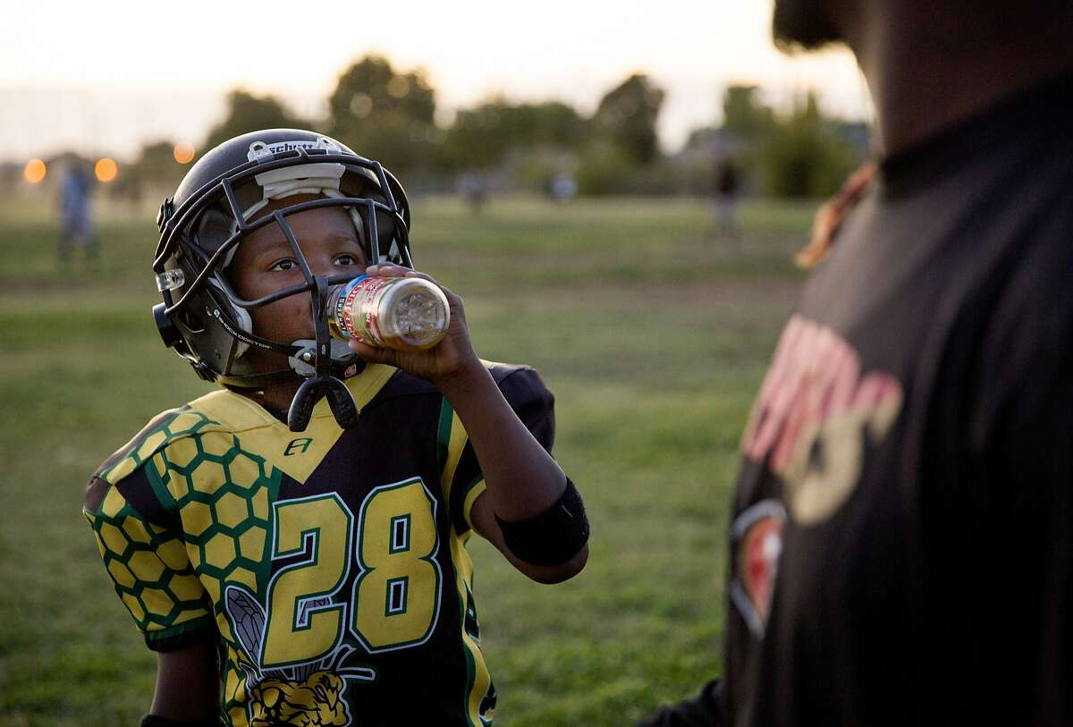 From left: Jamahl Mackey looks over to his father, Jamahl, during the Sacramento Jr. Hornets football practice as his father gives him tips on Thursday, Sept. 28, 2017, in Sacramento, Calif.