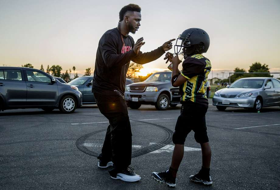 Jamahl Mackey gives his son, Jamahl Jr., football tips during team practice for the Sacramento Jr. Hornets. Photo: Santiago Mejia, The Chronicle
