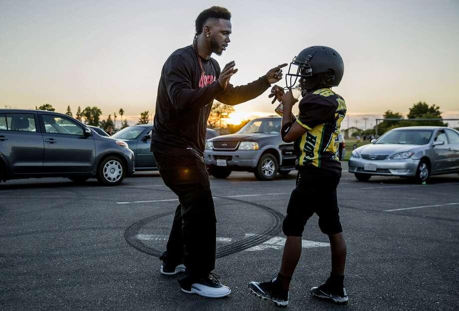 Jamahl Mackey gives his son, Jamahl Jr., football tips during team practice for the Sacramento Jr. Hornets. Photo: Santiago Mejia, The Chronicle