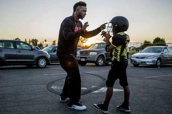From left: Jamahl Mackey gives his son, Jamahl, football tips during team practice for the Sacramento Jr. Hornets fotball team on Thursday, Sept. 28, 2017, in Sacramento, Calif.