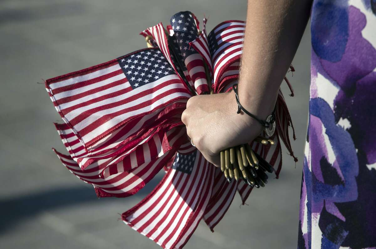 A congressional staffer holds a handful of small American flags to pass out as Democratic members of the House of Representatives rally for action on gun safety legislation after the deadly mass shooting in Las Vegas this week, at the Capitol in Washington, Wednesday, Oct. 4, 2017. (AP Photo/J. Scott Applewhite)