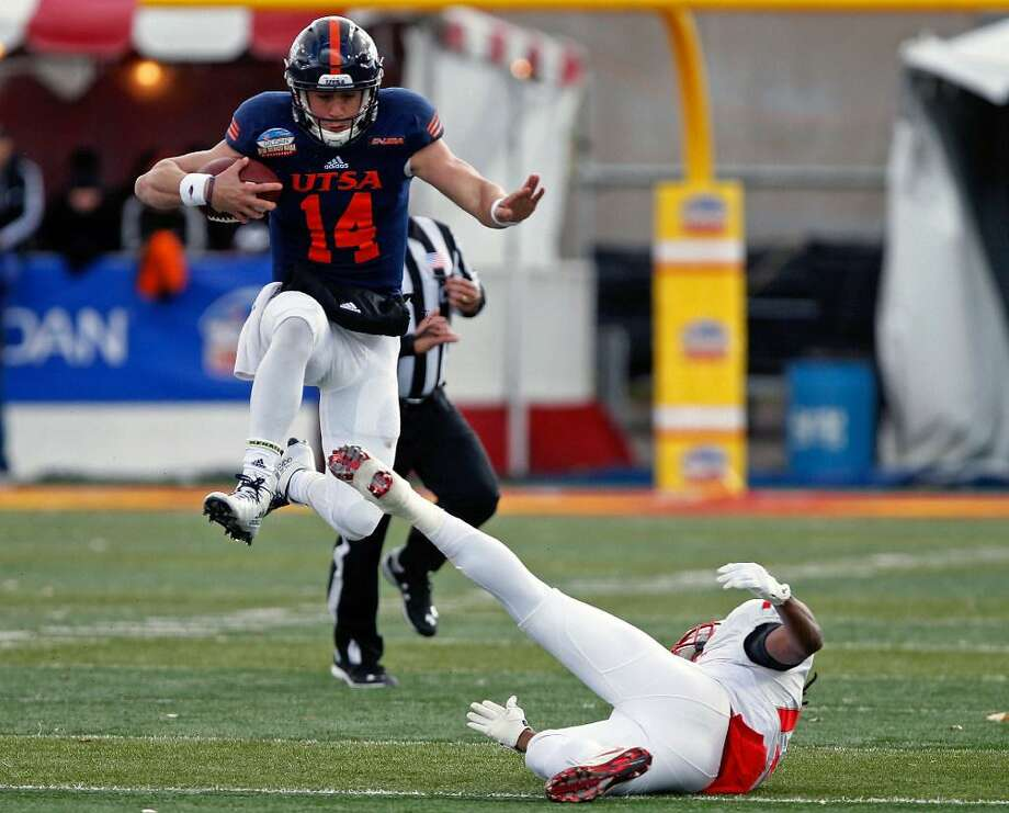 UTSA quarterback Dalton Sturm (14) leaps over New Mexico safety Ryan Santos to pick up extra yardage during the second half of the New Mexico Bowl NCAA college football game in Albuquerque, N.M., Saturday, Dec. 17, 2016. Photo: Andres Leighton /AP Photo