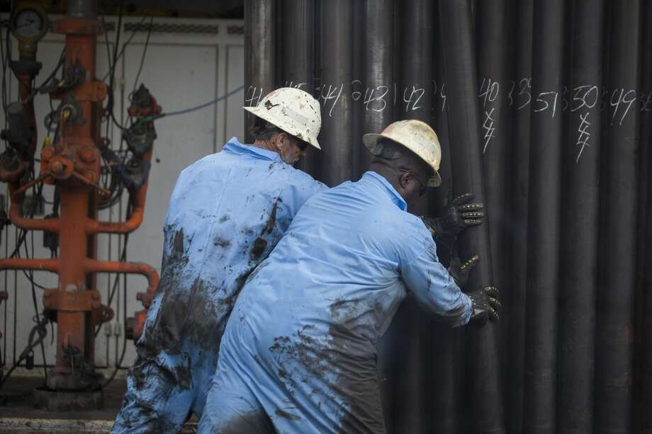 A oil rig workers set back a drill pipe vertically after being pulled out of a oil well hole, Tuesday, May 9, 2017, near College Station. ( Marie D. De Jesus / Houston Chronicle ) Photo: Marie D. De Jesus/Houston Chronicle