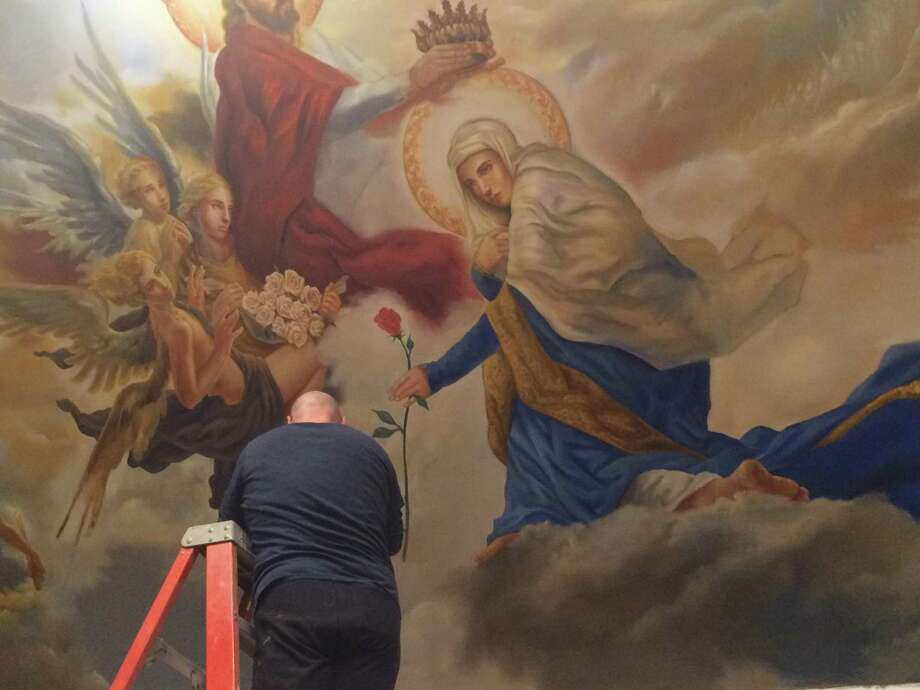 Paul Armesto paints his version of the Coronation of Mary by Christ on one side of the Assumption Church Chapel's ceiling in Ansonia. Photo: / Michael P. Mayko