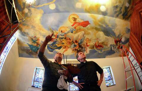 <p>Painter Paul Armesto, of Queens, points out details to Rev.