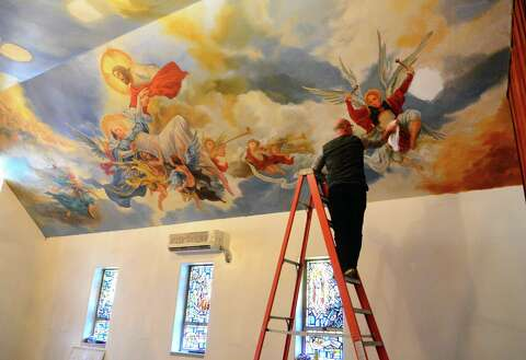 Painter Paul Armesto, of Queens, paints a mural depicting the Assumption and Coronation on