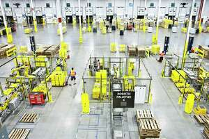 Employees work alongside robots at an Amazon warehouse in Florence, N.J., Aug. 29, 2017. Amazon is on the forefront of automation, finding new ways of getting robots to do the work once handled by human employees. (Bryan Anselm/The New York Times)