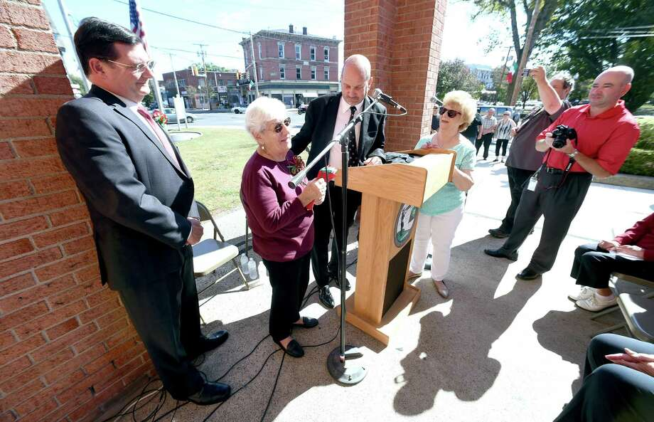 From left, West Haven Mayor Edward O'Brien watches West Haven Italian-American of the Year Grace Iannucci Hendricks receive an Italian flag from Paul Frosolone, president of the West Haven Italian American Civic Association, in front of City Hall Friday. Photo: Arnold Gold / Hearst Connecticut Media / New Haven Register