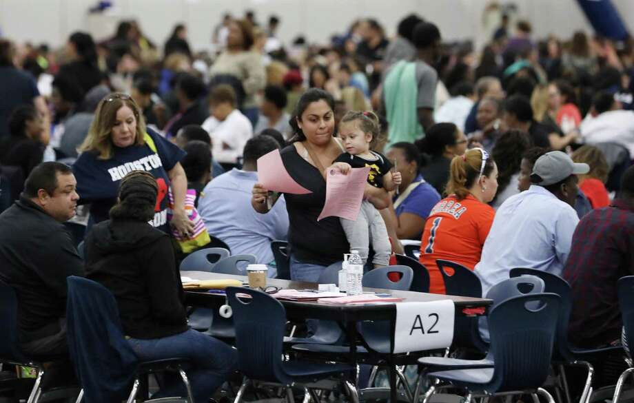 People complete paperwork to apply for emergency food assistance Friday at the George R. Brown Convention Center. Church leaders and nonprofit groups Friday demanded that Gov. Greg Abbott and others extend the application deadline for Texans who suffered because of Hurricane Harvey. Photo: Jon Shapley /Houston Chronicle / Houston Chronicle