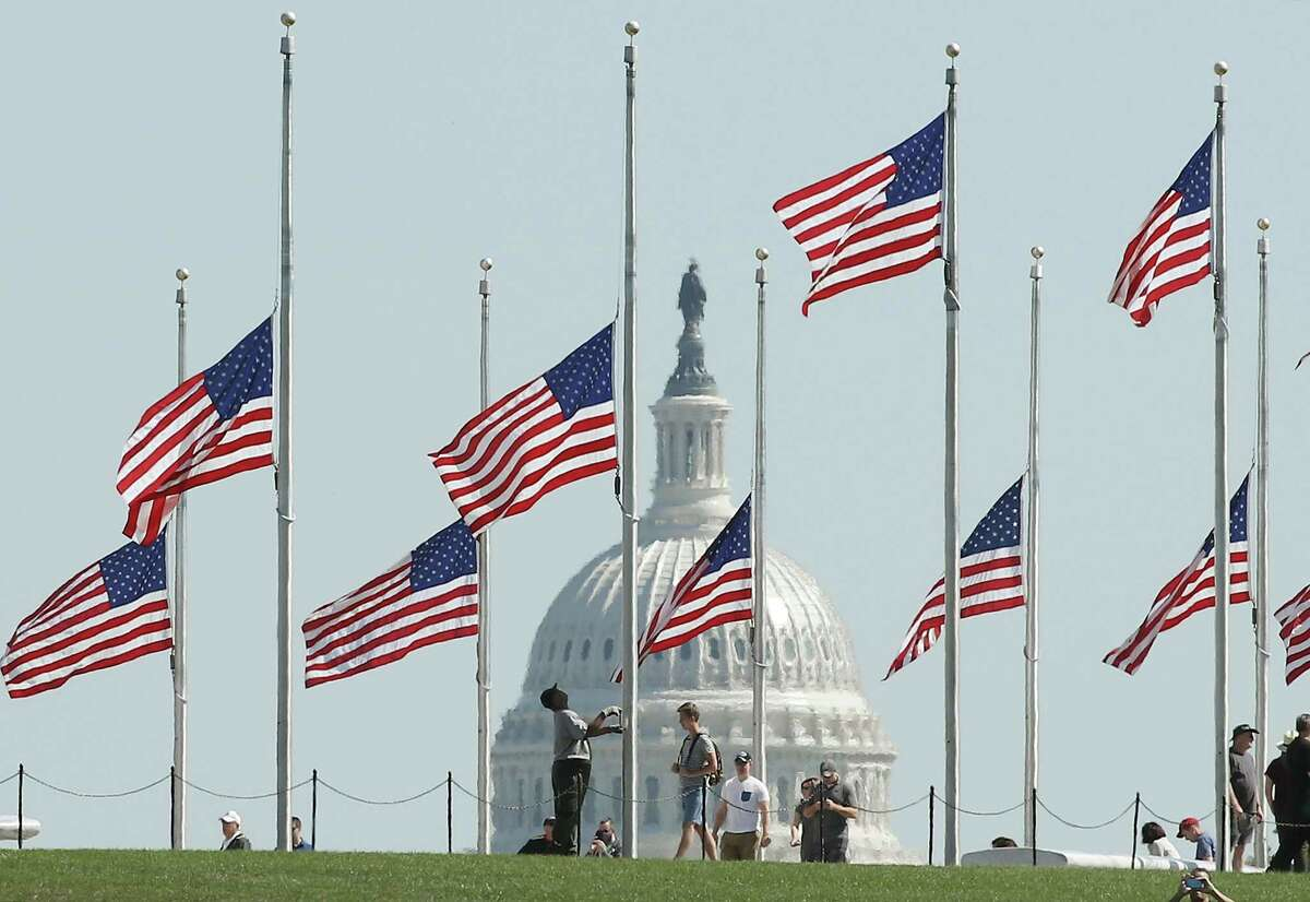 A Park Service employee lowers the U.S. flags on the grounds of the Washington Monument to half-staff.
