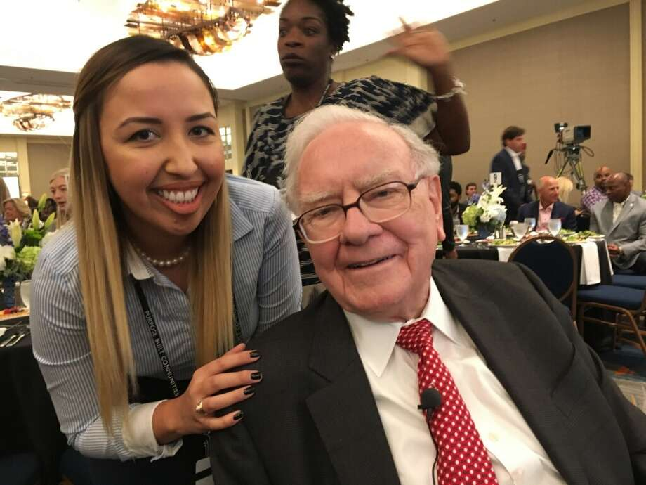Jessica Perez of Houston's Legacy Community Health huddles with Warren Buffett.