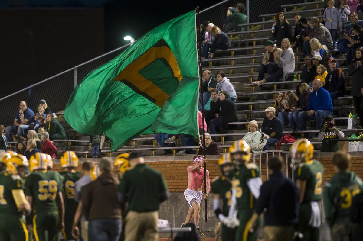 Dow senior Adam Hancock runs along the bleachers with a large flag after a touchdown during Dow's homecoming game against Arthur Hill on Friday, Oct. 6, 2017 at Midland Community Stadium. (Katy Kildee/kkildee@mdn.net)