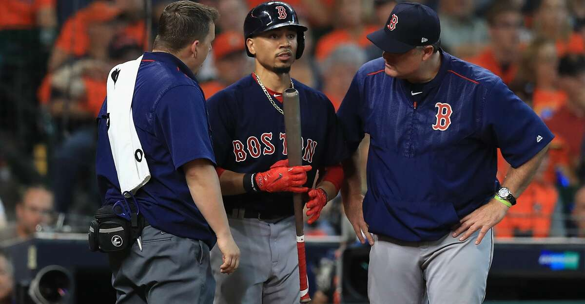 HOUSTON, TX - OCTOBER 06: Mookie Betts #50 of the Boston Red Sox is tended to by a trainer and manager John Farrell after experiencing pain in his wrist in the ninth inning against the Houston Astros during game two of the American League Division Series at Minute Maid Park on October 6, 2017 in Houston, Texas. (Photo by Ronald Martinez/Getty Images)
