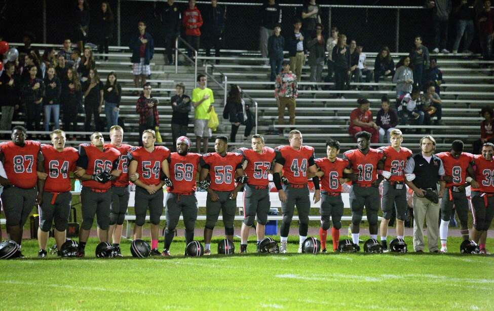 Niskayuna football players lock arms as they all stand for the national anthem is played before their game with Schenectady High Friday Oct. 6, 2017 in Niskayuna, NY. (John Carl D'Annibale / Times Union)