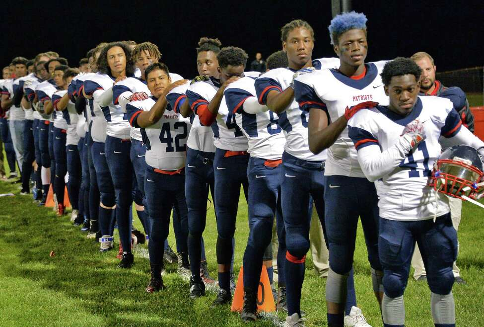 Schenectady High football players stand with hands on each other's shoulders during the playing of the national anthem before their game with Niskayuna Friday Oct. 6, 2017 in Niskayuna, NY. (John Carl D'Annibale / Times Union)