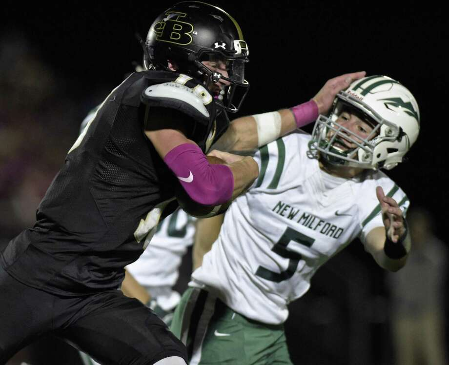 Barlow's Trevor Furrer (18) tries to push his way past New Milford's Austin Swanson Friday night. Photo: H John Voorhees III / Hearst Connecticut Media / The News-Times