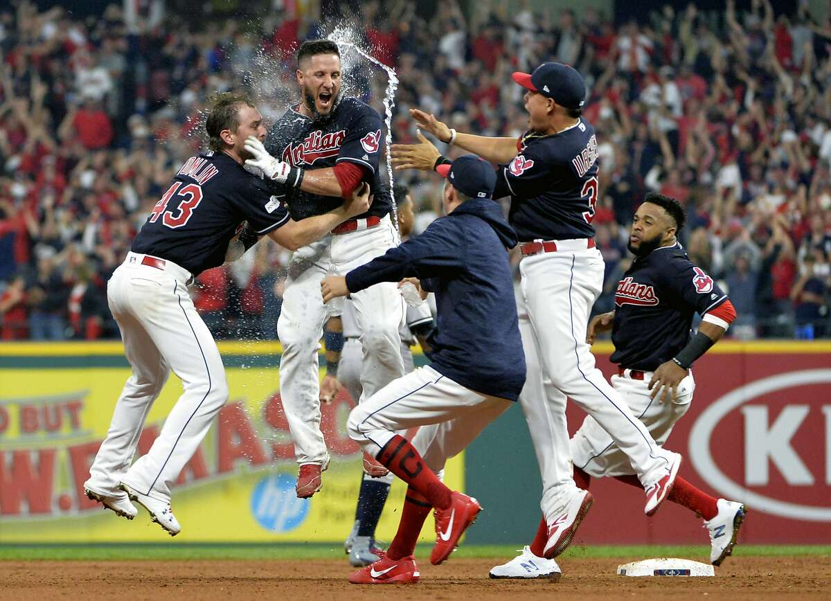 Cleveland Indians' Yan Gomes, second from left, is hugged by pitcher Josh Tomlin and mobbed by teammates after Gomes hit a game winning RBI-single in the 13th inning of Game 2 of baseball's American League Division Series against the New York Yankees, Friday, Oct. 6, 2017, in Cleveland. Austin Jackson scored on the play. The Indians won 9-8. (AP Photo/Phil Long)