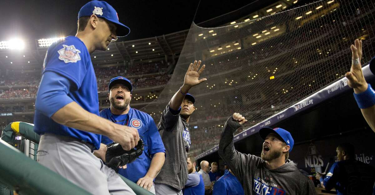 Chicago Cubs starting pitcher Kyle Hendricks, left, is greeted by teammates in the dugout at the end of the seventh inning in Game 1 of baseball's National League Division Series against the Washington Nationals at Nationals Park, Friday, Oct. 6, 2017, in Washington. (AP Photo/Pablo Martinez Monsivais)