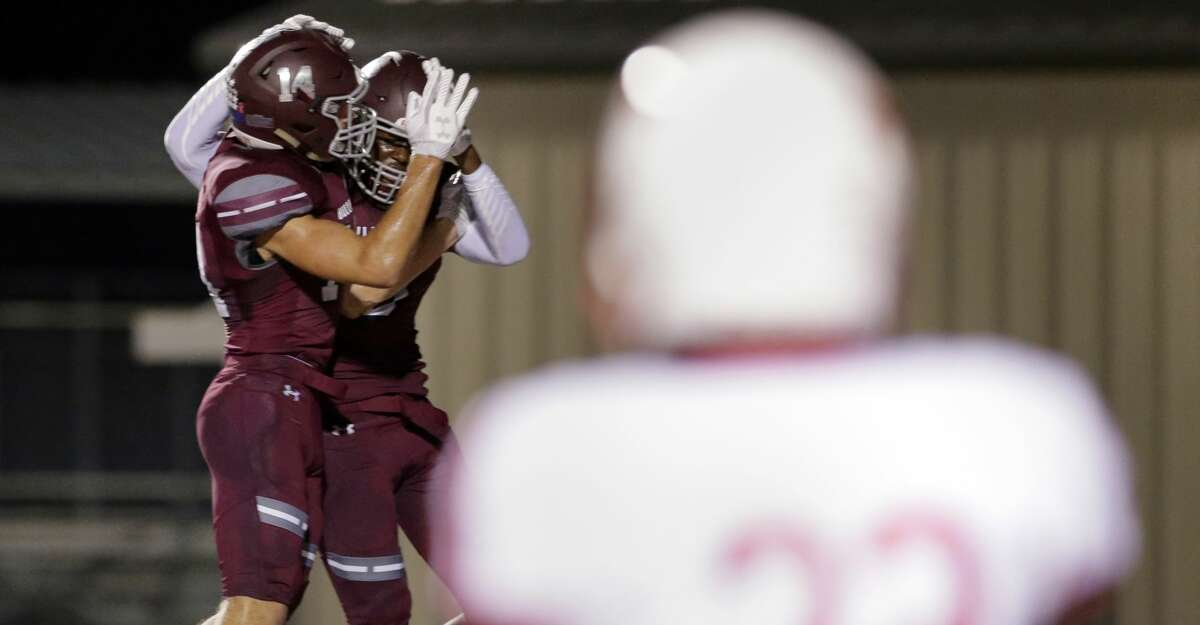 Magnolia's Ben Renfro (left) celebrates the touchdown by Michael Woods as Tomball's Dezmun Martinez looks on in the first half of their game at Bulldog Stadium in Magnolia, TX, Oct. 5, 2017. (Michael Wyke / For the Chronicle)