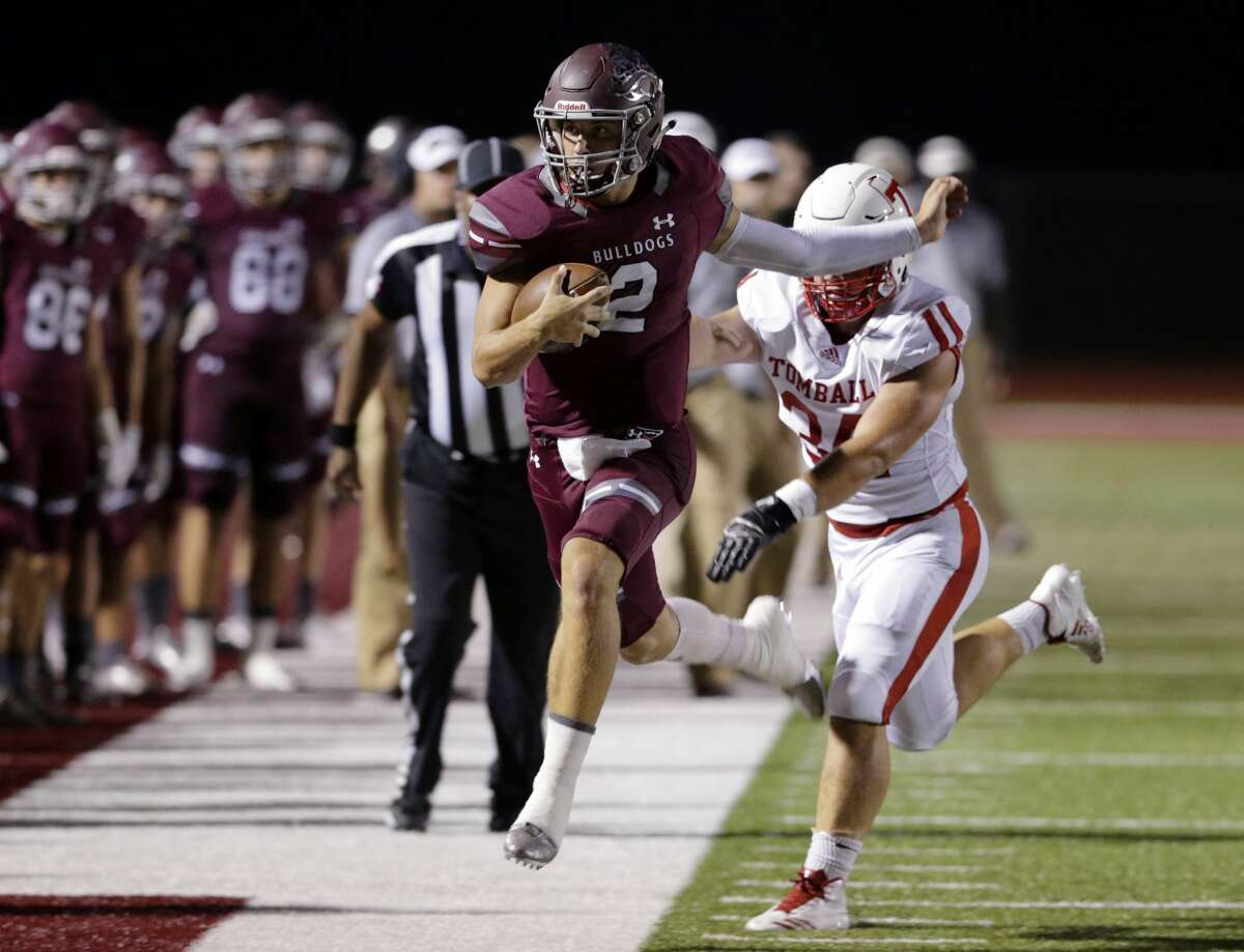 Magnolia quarterback Reese Mason is pushed out of bounds by Tomball's Dakota Stirman in the first half of their game at Bulldog Stadium in Magnolia, TX, Oct. 5, 2017. (Michael Wyke / For the Chronicle)