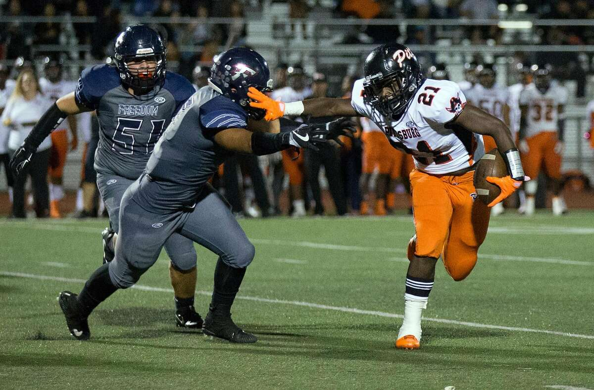 Pittsburg�s Darrion Bartley (21) stiff arms Freedom�s Kanin Wolfe (56) as he runs for a first down during the first quarter of a high school football game, Friday, Oct. 6, 2017 in Oakley, Calif.