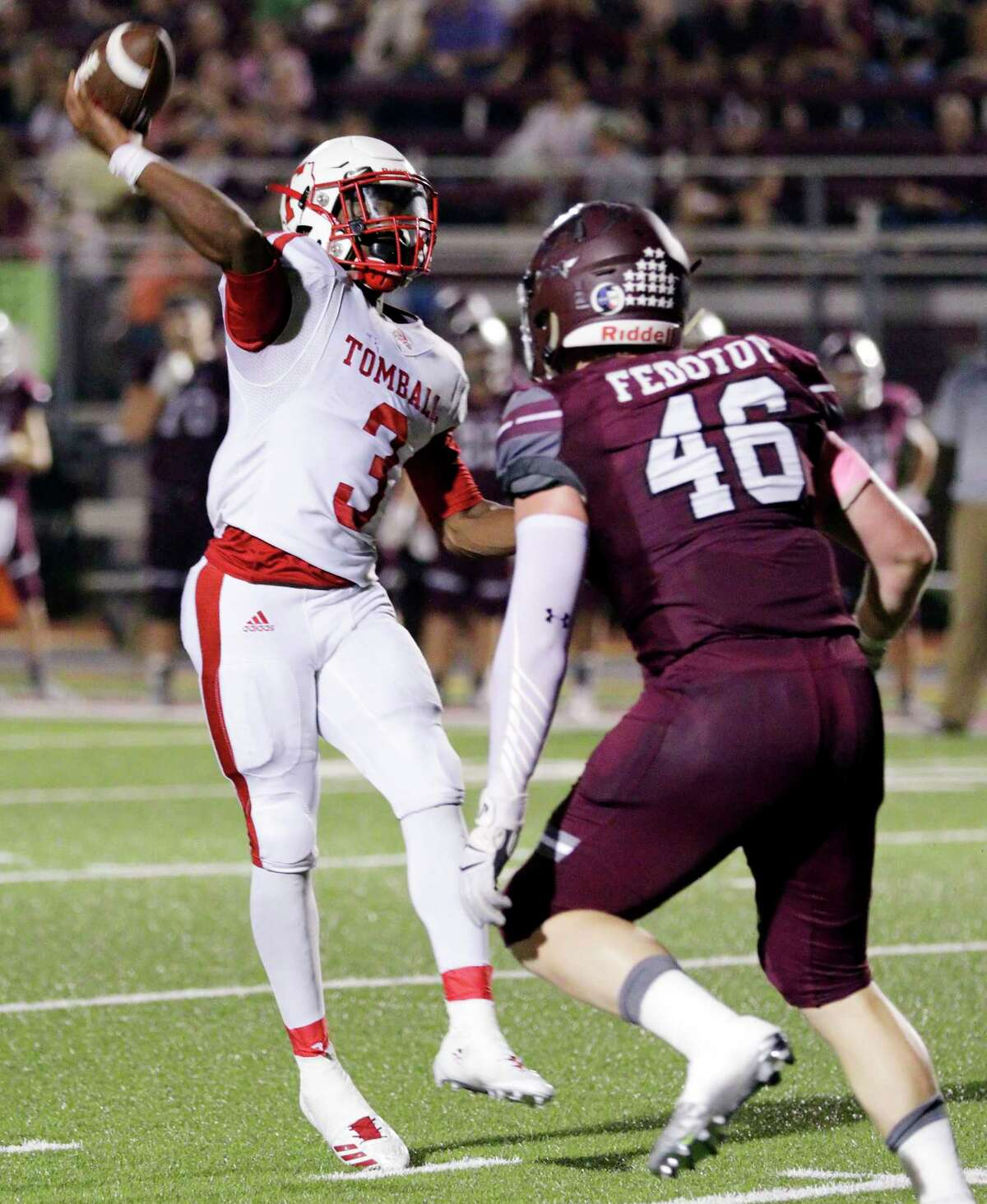 Tomball quarterback Tybo Taylor passes under pressure from Magnolia's Michael Fedotov in the second half of their game at Bulldog Stadium in Magnolia, TX, Oct. 5, 2017. (Michael Wyke / For the Chronicle)