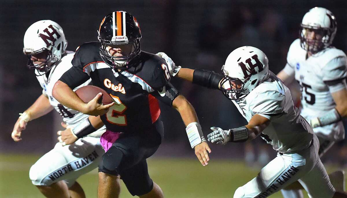 Shelton quarterback Jake Roberts avoids a tackle attempt by North Haven Vincent Campagnuolo (44) and Joe Deprimo (54), left and runs in for a touchdown, Friday, Oct. 6, 2017, at Finn Stadium at Shelton High School. Shelton won, 31-20.