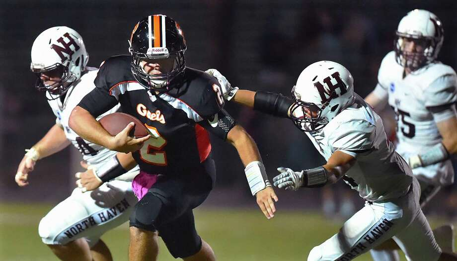 Shelton quarterback Jake Roberts avoids a tackle attempt by North Haven Vincent Campagnuolo (44) and Joe Deprimo (54), left and runs in for a touchdown, Friday, Oct. 6, 2017, at Finn Stadium at Shelton High School. Shelton won, 31-20. Photo: Catherine Avalone / Hearst Connecticut Media / New Haven Register