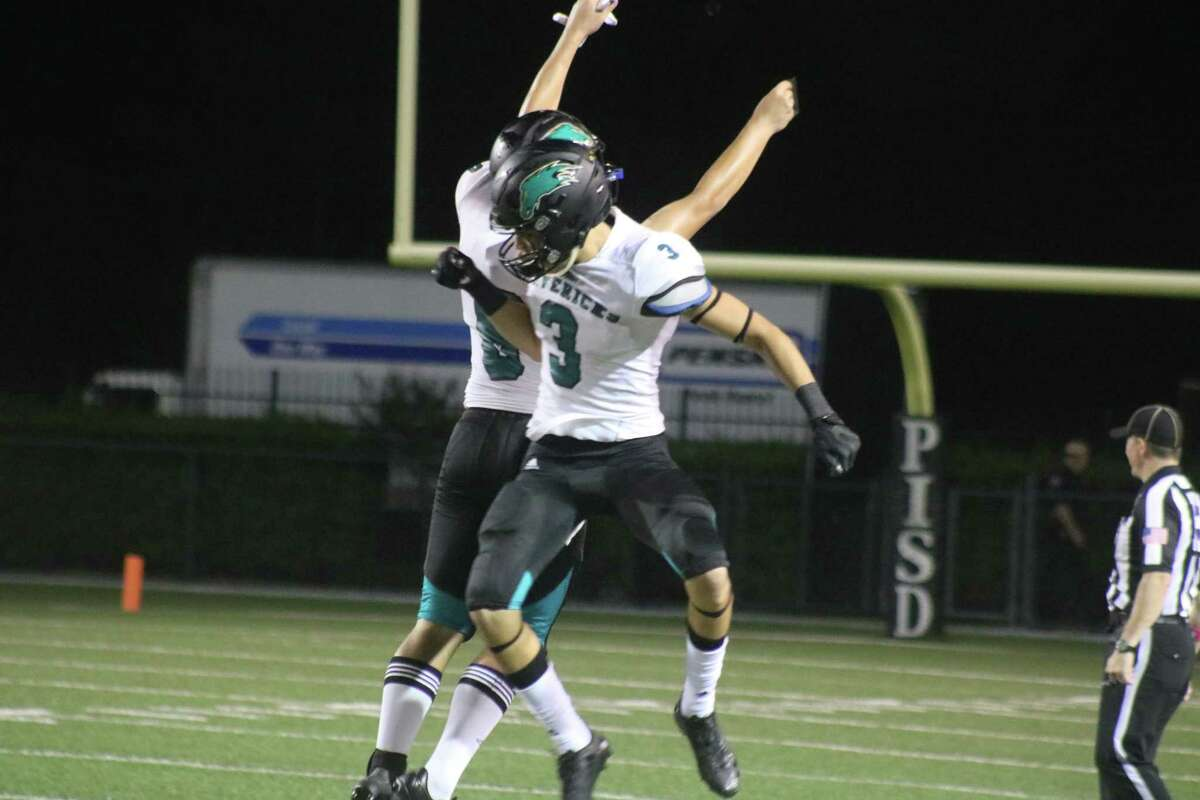 Joseph Campbell leaps in the air to help Bubba Baxa celebrate his 54-yard field goal in the second quarter.