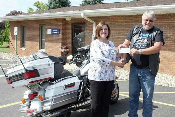 Motorcycle enthusiasts from near and far gathered at The Inn Between Saloon in Port Hope for the annual Dillinger Ride.(Right)ABATE Region 7 Chairman Tim Polk recentlypresented United Hospice Service representative Becky Heminger with a donation for the hospice program. (Submitted Photo)