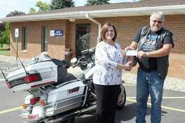 Motorcycle enthusiasts from near and far gathered at The Inn Between Saloon in Port Hope for the annual Dillinger Ride. (Right) ABATE Region 7 Chairman Tim Polk recently presented United Hospice Service representative Becky Heminger with a donation for the hospice program. (Submitted Photo)