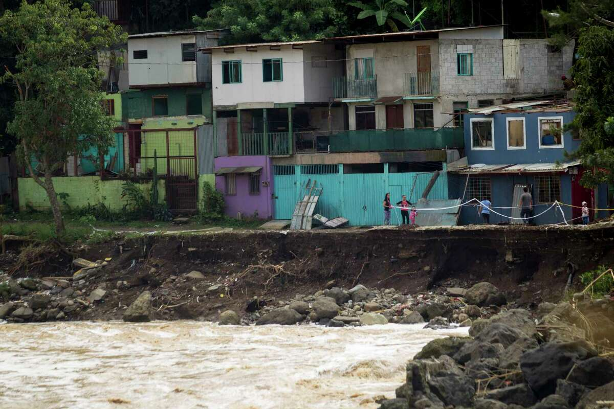 Residents stand between their damaged home and a street washed away by the heavy rains brought on by Tropical Storm Nate, on the outskirts of San Jose, Costa Rica, Friday, Oct. 6, 2017. Nate gained force as it sped toward Mexico's Yucatan Peninsula Friday after drenching Central America in rain that was blamed for at least 21 deaths.