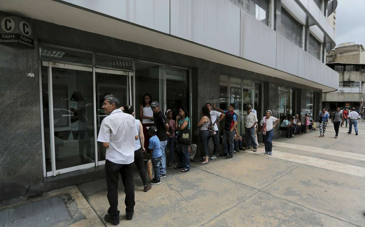 In this Sept. 23, 2017 photo, customers lineup outside of a bank to get cash, in Caracas, Venezuela. Venezuelans already struggling to find food, medicine and other basic necessities have a new headache to worry about: shortages of cash. Troubling shortfalls of Venezuelan bolivars are forcing many in this distressed South American nation to gather in long lines outside banks to take out what little cash is available. (AP Photo/Fernando Llano)