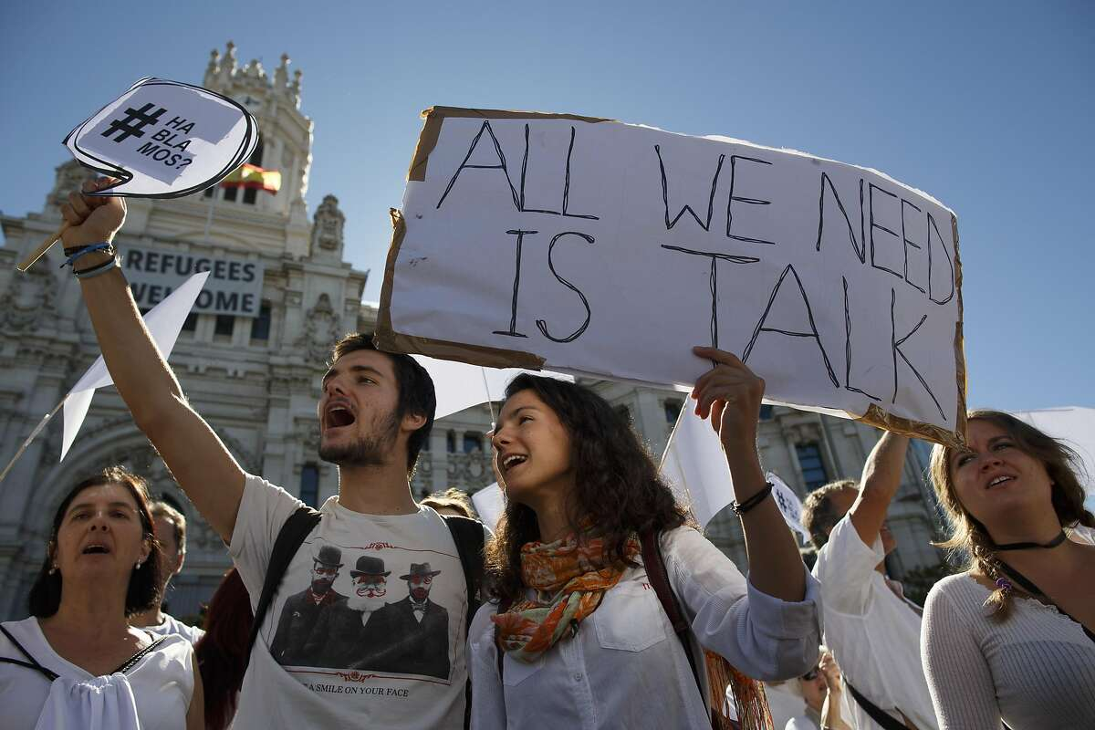 MADRID, SPAIN - OCTOBER 07: Demonstrators shout slogans and hold placards reading 'Do we talk?' (L) and 'All we need is talk' (R) during a protest in front of Madrid City Hall under the slogan 'Hablemos' in Spanish, 'Parlem' in Catalan or 'Let's talk' in English on October 7, 2017 in Madrid, Spain. After the indepence vote in Catalonia, an group of people called to demonstrate in front of all city halls to ask Catalan and Spanish goverments for dialogue to tackle the Catalonian independence issue. Demonstrator are asked to wear white clothes and protest. (Photo by Pablo Blazquez Dominguez/Getty Images)
