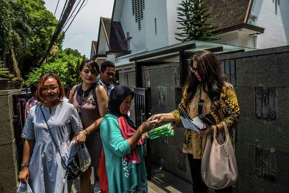 A Muslim woman sells tissue outside the entrance to St. Paul's Church in in Jakarta, Indonesia. The church was built in 1936 under the Dutch colonial administration.