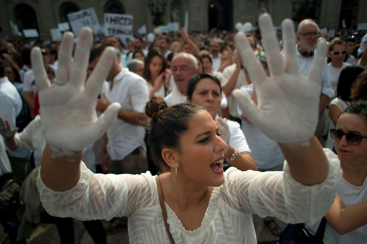 A woman shows her hands painted in white during a demonstration called by the