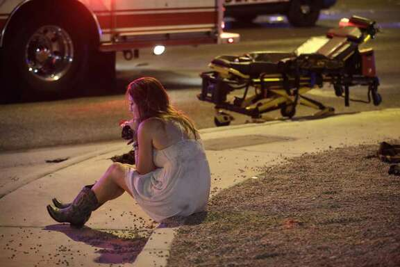 A woman sits on a curb at the scene of the mass shooting at a music festival  in Las Vegas.